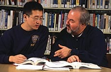 Asian male student reviewing book at a table with an older white male  professor